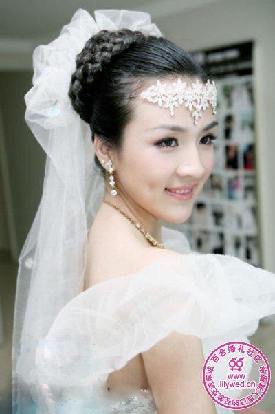 花朵形状组成的发饰点缀在新娘额前,编成的发辫盘在头顶,花朵形状的头纱将新娘的高贵表现的淋漓尽致