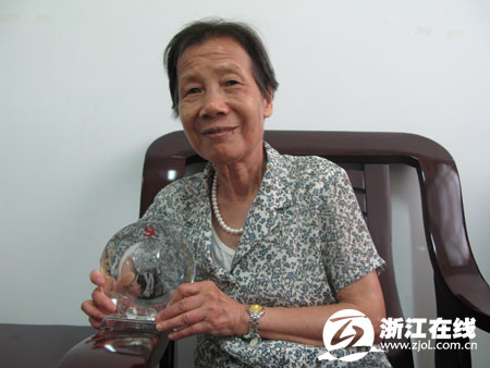 梁舜华捧着入党50周年纪念杯,平静的眼神中带着自豪与感动