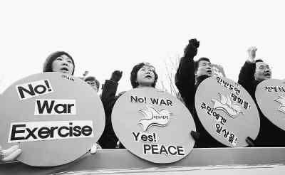 12月20日,部分韩国民众在首尔举行示威,抗议韩国在延坪岛附近海域举行实弹射击训练。图为一些民众手举标语牌在韩国国防部门口参加抗议活动。新华社记者 何璐璐摄