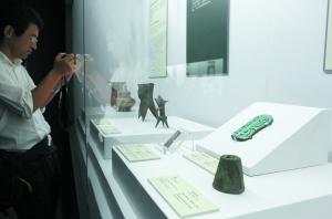 参观者正在欣赏、拍摄绿松石龙形器。