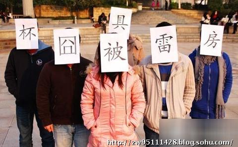 """2010年9月12日上午10时许,武汉商业服务学院的一位大三学子,凭借自制的一艘全部以纸为原料的小船,成功横渡汉江。图为在岸上的同学拉起横幅""""哥造的不是纸船是低碳""""的横幅,表示祝贺。"""