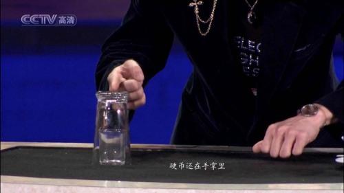看似很娴熟地把小玻璃杯放到桌面上,其实是非常仔细地放到出口的旁边,这个位置要使硬币出口处于小玻璃杯底座和大玻璃杯口之间.刘谦可以用右手或者脚启动一个隐蔽的开关,使弹簧机构动作将硬币弹射上去,这个机关我们不去思考了,因为根本不用费脑筋,这不是魔术的关键.硬币弹射上去后,经过小玻璃杯的杯口和大玻璃杯的内杯壁之间的缝隙,上升到大玻璃杯的底座后,被反射回来,掉到小玻璃杯里.由于弹簧的发射速度快,硬币上升过程用肉眼根本看不出来,人们只是看到硬币瞬间在小玻璃杯里面,感到很惊奇.