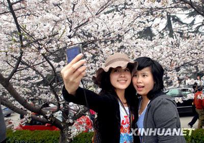 3月20日,两名游客在武汉大学校园内的樱花前拍照留念。新华社发