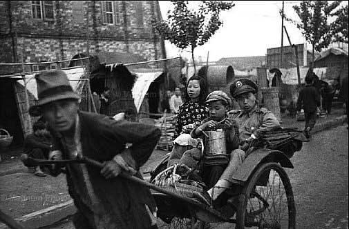 1949年4月,南京,带着家庭的财产外出逃亡的国民党军官,背景是数