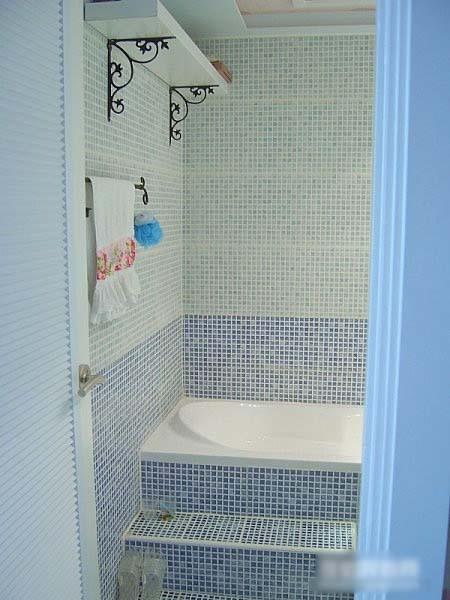 浴缸镶在马赛克里面了,上面按了隔板可以放些换洗衣物。