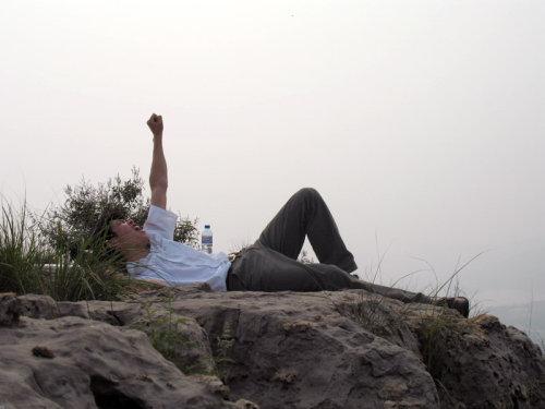 山顶的石头上,仰望天空,伸手去抓   有些东西看似很近,其实