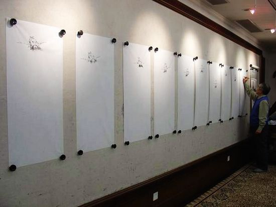 """一面大白墙上整齐地悬挂着十多张大幅宣纸,所有画面出现的都是相似的""""钟馗""""模样的古代人头像"""