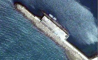 资料图片:美国商业卫星拍摄到的某国潜艇泊在基地码头内