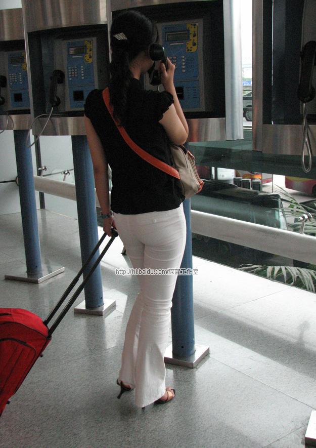 [紧身美臀]白色细牛仔裤mm拖着行李打电话