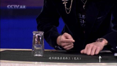 只是观众从摄像机的角度无法看到那枚硬币而已.整个过程结束了,刘谦直起腰,左手很自然地掌心向下,放在桌面上向左后方滑动,其实,左手掌下就压着那枚硬币,硬币随着手掌被滑到了桌子的边角了,桌角有笔,餐巾纸,玻璃盘等杂物的遮挡,根本看不到那枚硬币了!!!