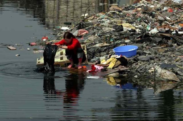 由于受到严重污染,这里的河水早已发黑变臭。然而孩子们还在水里嬉戏。在他们眼里,也许河水原本就是黑色的……