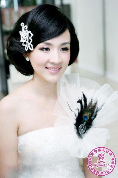 简洁的蝴蝶形状水晶发饰点缀在新娘俏丽短发上,与抹胸婚纱上羽毛遥相呼应