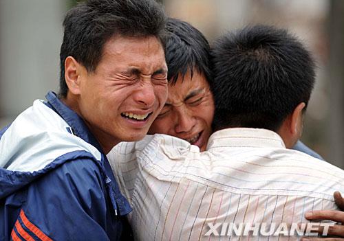 5月15日,在四川安县,三位困在大山里三天的灾民翻山越岭,艰难跋涉三十多公里终于走出大山后,情不自禁地抱头痛哭。